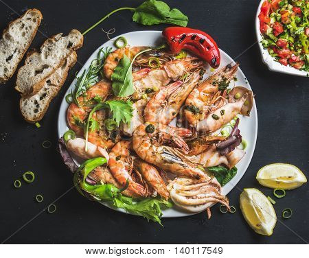 Plate of roasted tiger prawns and octopus with fresh leek, vegetable salad, peppers, lemon, bread and pesto sauce over black background, top view, horizontal composition