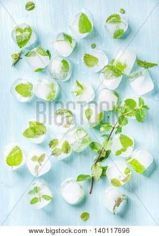 Ice cubes with frozen mint leaves inside on blue Turquoise background, top view, vertical