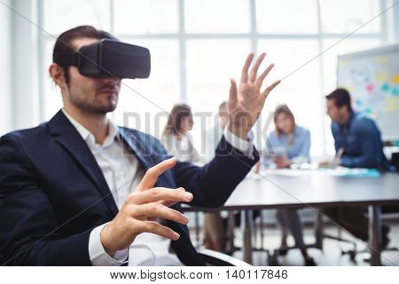 Businessman using virtual reality simulator against coworkers in meeting room at office