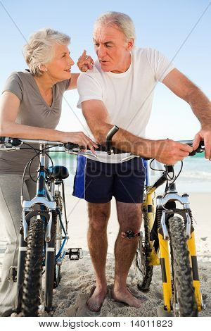 Retired Couple With Their Bikes On The Beach