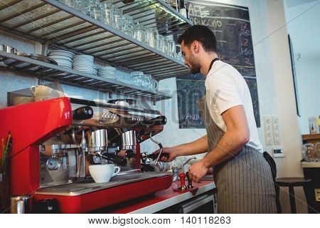 Side view of young male barista working by coffee maker at cafe