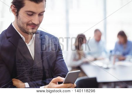 Businessman using smart phone in meeting room at office seen through glass