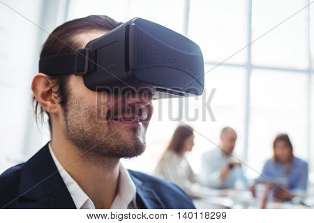 Smiling businessman using virtual reality simulator against colleagues in meeting room at office