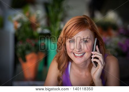 Female florist using mobile phone in the flower shop