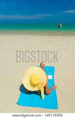 Fit woman in sun hat and bikini at the  beach