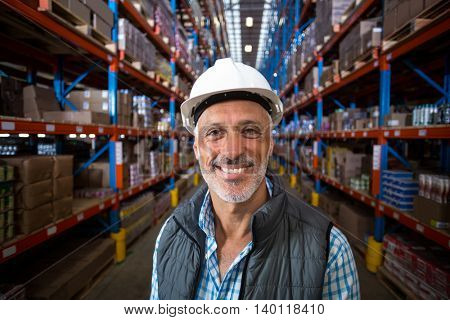 Portrait of happy worker smiling to the camera in a warehouse