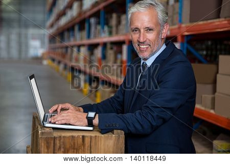 Business man posing for the camera in a warehouse