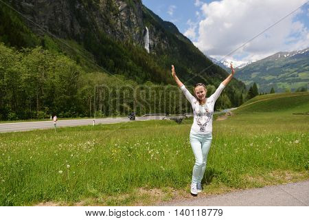 woman standing on winding road at foot of mountains