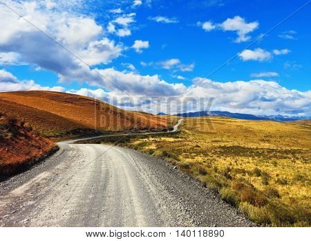 Magic country Patagonia. Gravel road between the colorful hills. National Park Torres del Paine in Chile