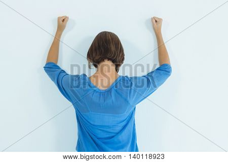 Rear view of sad woman standing against wall at home