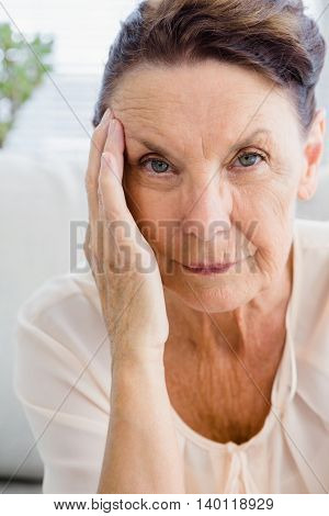 Portrait of woman having headache while sitting at home