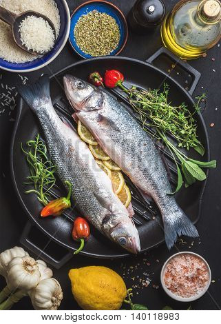 Ingredients for cookig healthy fish dinner. Raw uncooked seabass fish with rice, lemon, herbs and spices on black grilling iron pan over dark background, top view, vertical composition