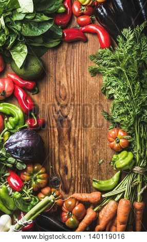 Fresh raw vegetable ingredients for healthy cooking or salad making over rustic wood background, top view, copy space, vertical composition. Diet or vegetarian food concept