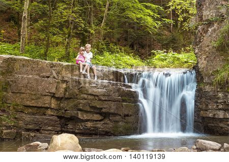 Two children boy and girl sitting near waterfall in forest
