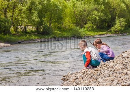 Children boy and girl playing near the river