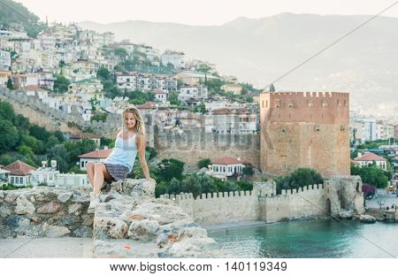 Young blond tourist woman sitting on ancient fortress wall of Alanya castle on sunset. Kizil Kule or Red Tower at background. Turkey, Mediterranean region