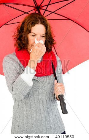 Mature woman suffering from cold while holding umbrella against white background