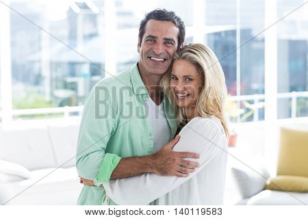 Portrait of mid adult romantic couple hugging at home