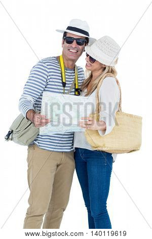 Happy mid adult couple holding map while standing against white background