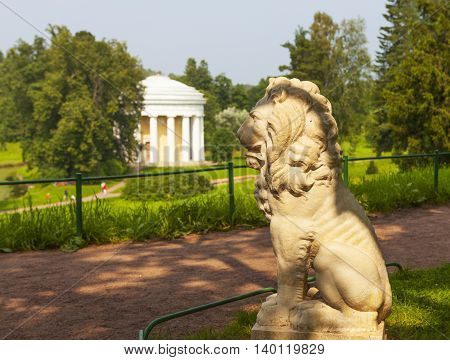 Pavlovsk. Sculpture of a lion on a background of the Temple of Friendship. Russia.