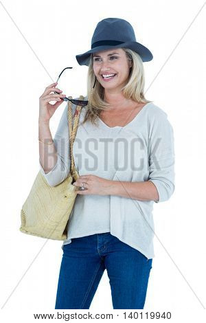 Happy mid adult woman holding sunglasses against white background