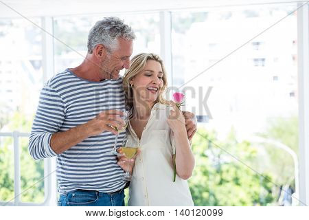 Romantic mature couple with wine glasses and rose while sitting at restaurant