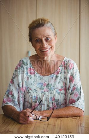 Portrait of a smiling senior woman holding glasses seated on a table