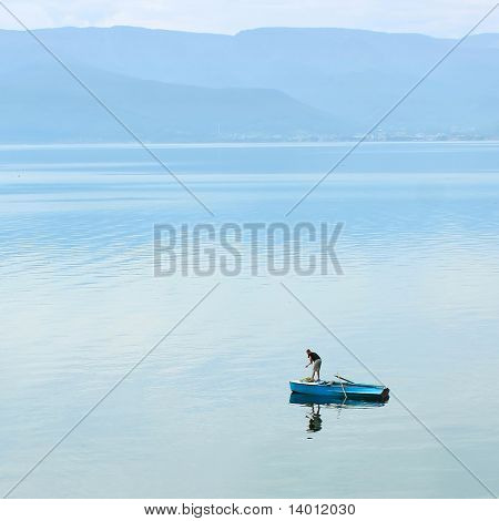 Alone fisherman on huge lake in little boat