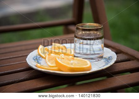 vodka and oranges at the plate on the stool