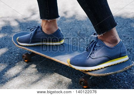 Feet of young man skateboarding in the city