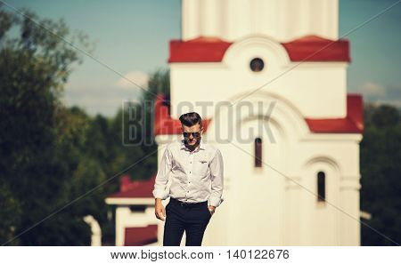 Portrait of stylish handsome young man with bristle standing outdoors. Man wearing pants and shirt.