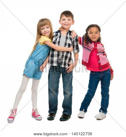 three smiling little children standing together isolated on white background