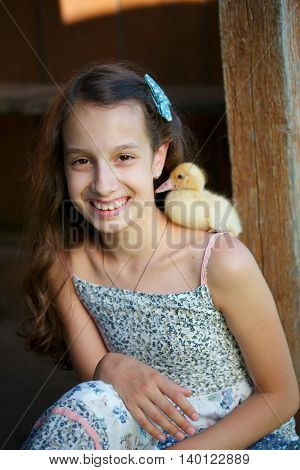 young girl with little yellow duckling in summer village