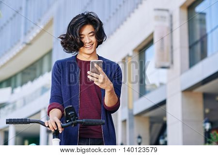 Cheerful asian man with bicycle reading message on his phone