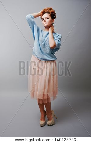 Full Length Studio Portrait Of Young Red Haired Curly Girl At Blue Blouse And Pink Skirt
