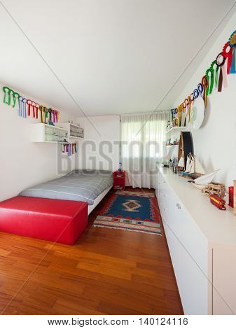 Interior, teens room of a house, single bed and white walls