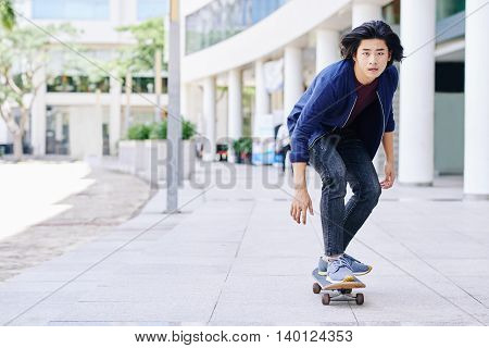 Vietnamese young guy skateboarding in the city