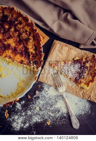 Traditional italian sweet fresh round bright homemade pie Crostata with jam in baking dish on wooden table with topping of powdered sugar. Baking. Top view.