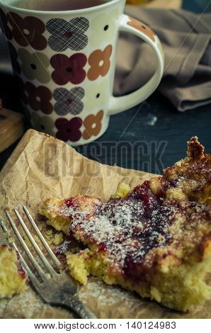 Slice of traditional italian sweet fresh round bright homemade pie Crostata with jam and topping of powdered sugar. Cup of tea. Breakfast. Baking. Selective focus.