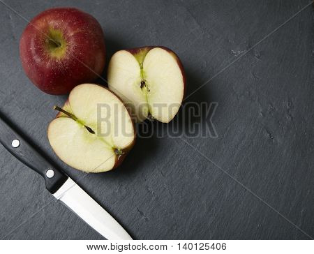 Halved apples with a sharp knife on a rustic slate chopping board background forming a page border
