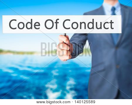 Code Of Conduct - Businessman Hand Holding Sign