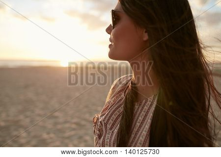 Close up shot of beautiful young woman with sunglasses looking away at a view. Caucasian female model on the sea shore at sunset.