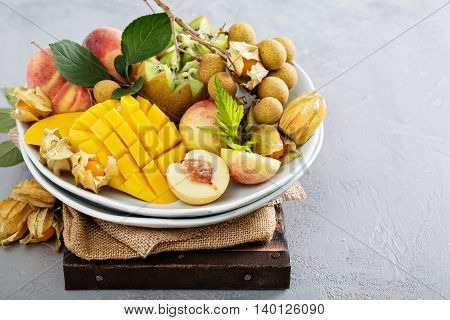 Assorted fresh ripe tropical fruits on a plate including mango, longan, kiwi and gooseberries