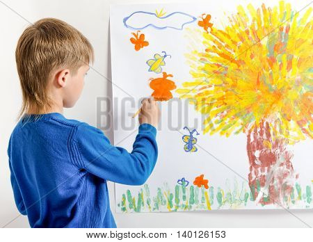 Young boy draws a picture. Back view