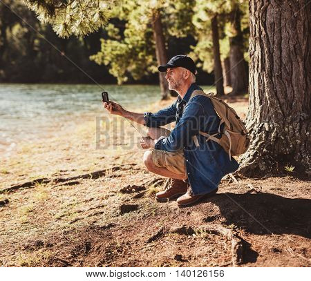 Senior Man At A Lake Using Compass For Searching Direction