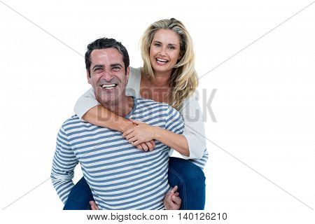 Portrait of man carrying woman piggyback against white background