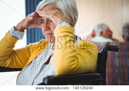 Senior woman in wheelchair look worried with her hands on her forehead