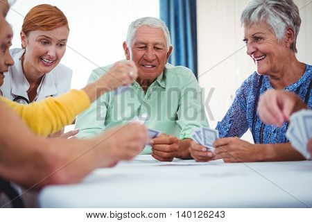 Smiling nurse and seniors people playing cards in a retirement home