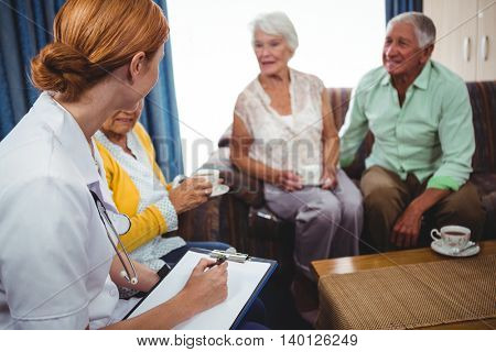 Seniors peoples and nurse seated in a sofa chatting together