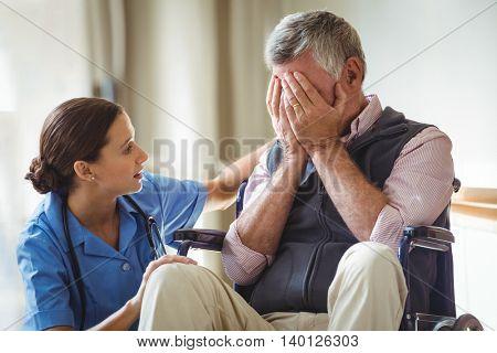 Nurse taking care of sad senior man in a retirement home
